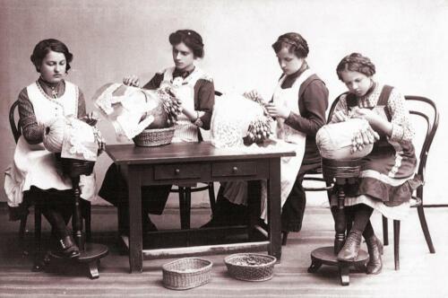 Starší žákyně, používající k práci typické stojánky a podušky s vambereckými paličkami
